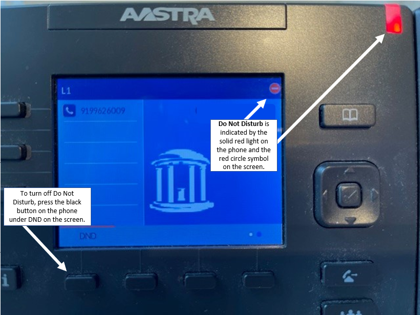 """Photo of Mitel phone with """"Do Not Disturb"""" indicated by the solid red light on the upper right hand corner of the phone and the red circle symbol on the upper right hand corner of the screen. Note to press the left button under the screen to turn off Do Not Disturb."""